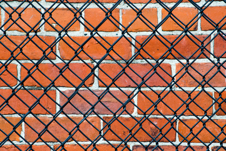 A chain link fence usually means security, do not enter, protection  the brick wall makes you wonder what is being protected