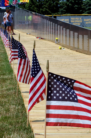 People view names of those who paid the ultimate price of war  this is the vietnam traveling wall memorial that moves throughout the USA  the american flags remind us that freedom is not always free photo
