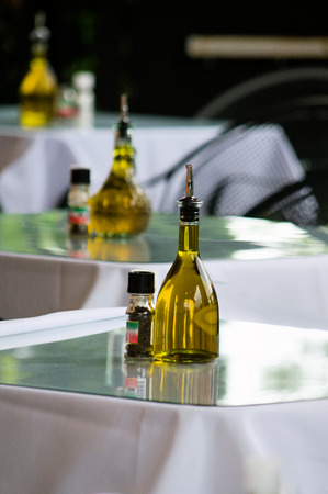glass topped: Bottles of amber olive oil sit on glass topped tables in an italian restaurant Stock Photo
