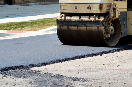 flatten: A machine used to flatten and smooth hot asphalt, is smoothing out a new road