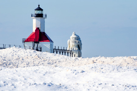 A light house in Michigan, looks like a white sugar frosted sculpture, as its covered in ice and snow  photo
