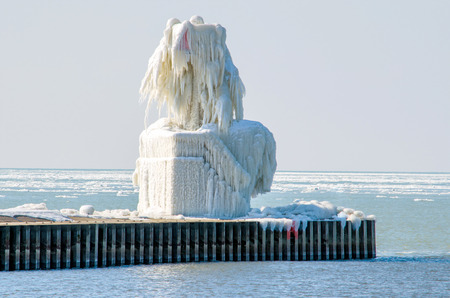 an ice covered light beacon looks like a frozen sculpture on the endge of lake michigan photo