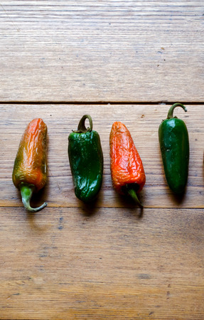 Red and green hot peppers are lined in a row on a weathered wood background