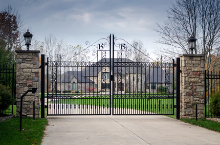 A large fancy house sits behind a gated entry, a sign of privilege and money Editorial