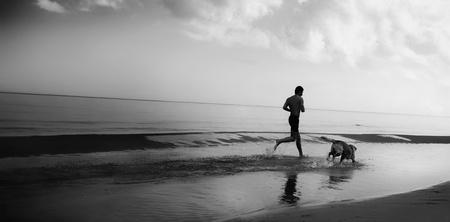 personas corriendo: Un hombre que se ejecutan con un perro en la orilla del mar Foto de archivo