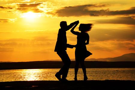 日没でサルサを踊るカップル 写真素材