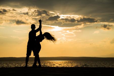 Paar dat bij zonsondergangsalsa  Braziliaans zouk danst. Liefhebbers, danspartners spinnen, Latijns-festival dans concept Stockfoto