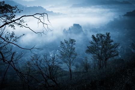Mysteriöser nebelhafter Morgen über Birtan-Dorf, Siebenbürgen, Rumänien. Blaue Farben. Halloween Postkarte Konzept. Standard-Bild