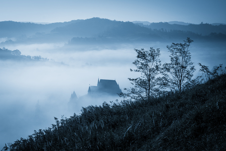halloween background: Mysterious misty morning over Biertan village, Transylvania, Romania. Blue colors. Halloween postcard concept.