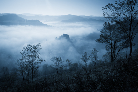 Mysterious misty morning over Biertan village, Transylvania, Romania. Blue colors. Halloween postcard concept.