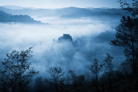 Mysterious misty morning over Biertan village, Transylvania, Romania. Blue colors. Halloween postcard concept.