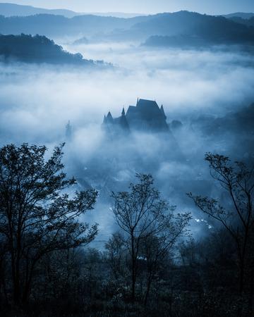 in monastery: Mysterious misty morning over Biertan village, Transylvania, Romania. Blue colors. Halloween postcard concept.
