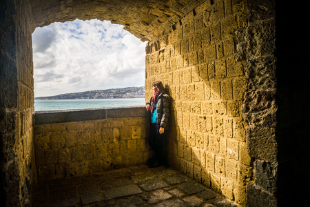 Tourist young girl sitting above the adriatic sea at the ruins of a fortress window