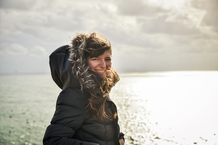 Girl in winter jacket by the sea. Wind blowing in her hair Stockfoto