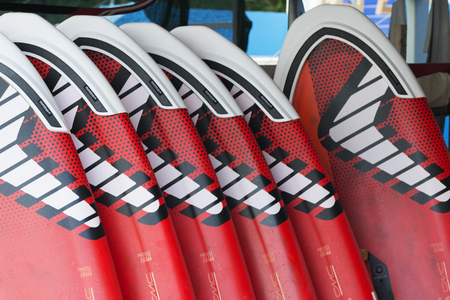 A bunch of red and white windsurfing boards