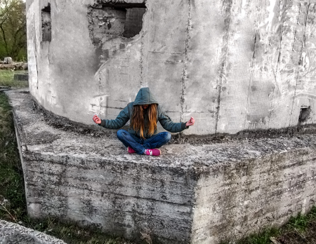 anorak: A girl with long blond hair in a hood sits in a lotus pose. She sits outdoors on a concrete wall and tilted her head down