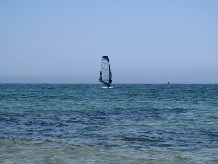 One windsurfer in the sea. Turquoise sea, clear blue sky without clouds and a surfer with a blue sail in the middle photo