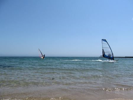 windsurfers: Two windsurfers with a blue and red sail in the sea. Water entertainment for sports people at sea or in the ocean