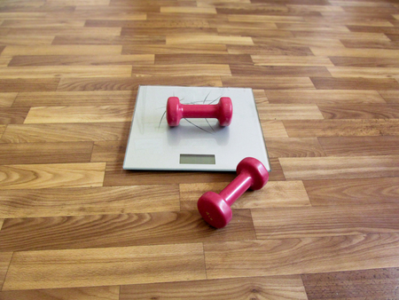 second floor: Two red dumbbells and electronic scales - the concept of excess weight. One dumbbell lies on a silver scales, and the second dumbbell lies on the brown floor near the scales