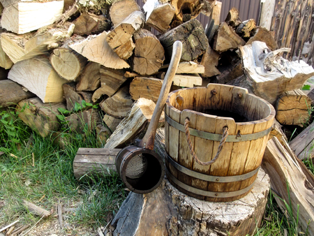 A wooden rural vintage bucket and a ladle on the background of a pile of firewood. Beautiful photo of rural lifestyle