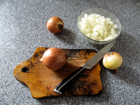 cutting: A bowl with chopped onions, three whole onions and a knife on a cutting board - the cooking stage. Gray spotted