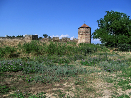 The tower of the Akkerman fortress (Ukraine) in the steppe against the background of a clear blue sky. One of the oldest landmarks in the Odesa region is the largest preserved castle on the territory of Ukraine - Bilhorod-Dnistrovskyi fortress