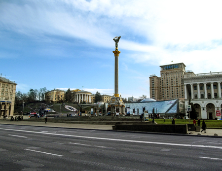 Kiev, Ukraine - December 31, 2017: Maydan Nezalezhnosti with the Independence Monument of Ukraine in the center - side view. Warm winter without snow in Kiev with bare trees, blue sky and people in the square in warm clothes