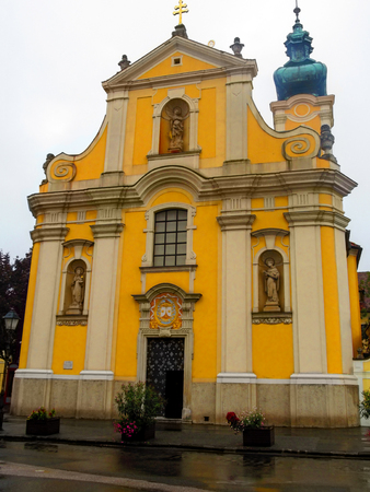 Facade of the Carmelite Church in Gyor (Hungary) from the front in a summer rainy day. Undistinguished yellow Baroque temple with a facade in an Italian style against the gray sky and wet from the rain of asphalt
