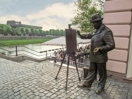 Ukraine, Uzhgorod - April 30, 2018: Ignatiy Roshkovych Monument on the background of the river Uzh in Uzhhorod. A bronze man in a hat with an easel paints a landscape on the river bank