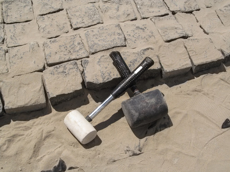 Two crossed rubber hammers lie on the unfinished laying of granite paving stones. Building background - the concept of laying paving slabs and pavers