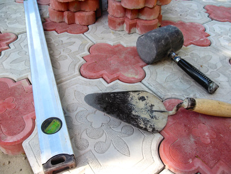 Rubber hammer, trowel and level on the backdrop of decorative red and white paving tiles close-up. Beautiful bright building background, concept of paving slab tiles
