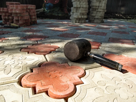 One black rubber Mallet lies on a newly laid red-and-white decorative paving slab. Work of laying a beautiful figured tile Clover patterned - a two colorful piles of paving slabs in the background Stok Fotoğraf