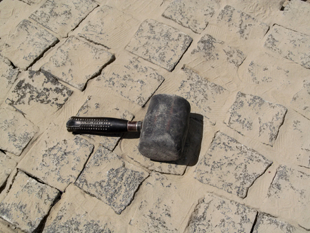 One black rubber mallet lies on a granite paving stones surface - a top view. The concept of works of landscaping such as laying paving slabs or paving granite pavers