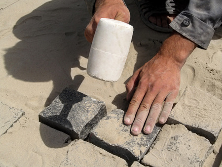 The worker strikes with a white rubber mallet on granite pavement stones. Male working hands hold a hammer and a paving stone