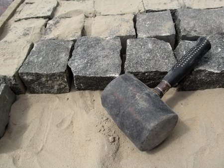 Black Mallet close-up on a background of square granite stones and sand. The concept of improving the sidewalks and yards