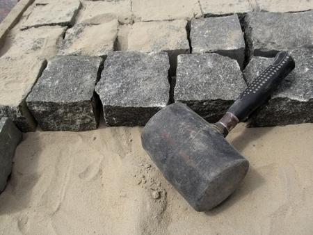 Black Mallet close-up op een achtergrond van vierkante granieten stenen en zand. Het concept van het verbeteren van de trottoirs en werven Stockfoto