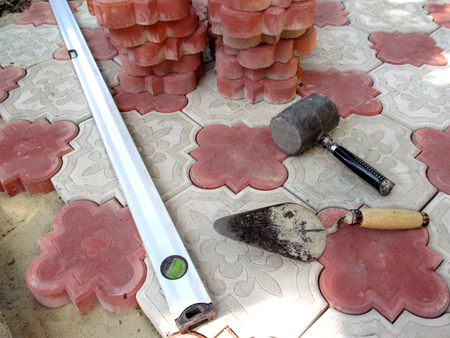 Tools for laying paving tiles close-up on a background of red and white figured stone blocks. Colorful wallpaper, the concept of laying paving slabs and the paving of granite pavers