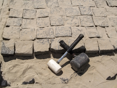 Two crossed rubber hammers lie on the stones of granite pavers - a top view. In the process of laying paving slabs - a beautiful building background or wallpaper