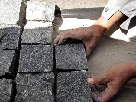 The working man paves gray cobbles of the granite paving stones. Male hands hold square stones and spread them evenly on sand
