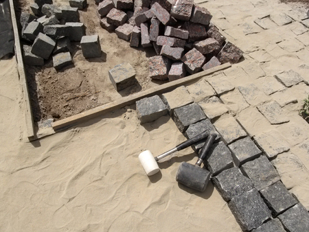 Workplace for laying granite paving stones - top view. Unfinished work on laying paving slabs - a pile of cobblestones, two rubber hammers and a sand-cement surface Stok Fotoğraf