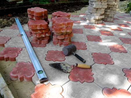 Work place for laying beautiful red and white figured paving slabs. Unfinished laying of paving slabs on the floor, a pile of red tiles, a building level tool, a trowel and a rubber mallet