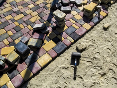 Installation of colorful bright paving slabs. Red, black and yellow sidewalk tiles Old Town and rubber mallet for work