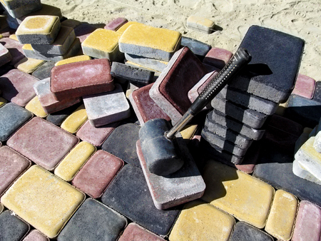 A pile of colored bricks of the tiles Old Town and a rubber hammer for laying paving slabs. Beautiful yellow, red and black rectangular blocks, bright wallpaper or background on the building theme