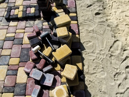 Unfinished work on laying colored paving tiles with rubber mallets. Beautiful colorful bright background, the concept of laying paving slabs Stok Fotoğraf