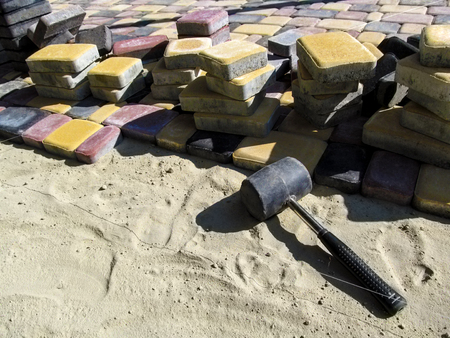 A stretched string (fishing line), a rubber hammer, a sand and a pile of multicolored paving slabs. Bright construction background, the concept of laying paving slabs in the yard Stok Fotoğraf