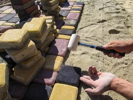 Mens hands install a colorful bright beautiful paving slab with a rubber mallet. Process of laying the sidewalk tile, a workplace with piles of tiles, sand-cement mix and stretched construction rope