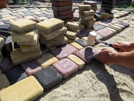 A man knocks on a multicolored sidewalk tile with a rubber mallet. Work on paving beautiful bright slabs on a patio or yard