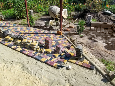 Yard landscaping with colorful beautiful paving slabs, unfinished work. Beautiful landscape of a patio with bright paving slabs, construction tools, curbs and flowers in the background