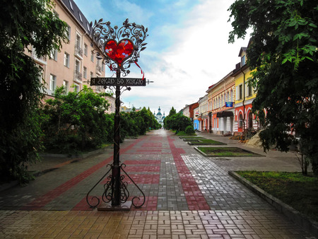 Ukraine, Sumy - May 31, 2014: Love Lantern on Voskresenska street in Sumy. Pedestrian street, an elegant forged pillar of lovers and a temple on the horizon Editöryel