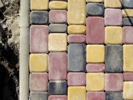 Bright colorful blank paving background, top view. The texture of the red, yellow and black bricks of paving slabs Old Town and the border on the background of the soil